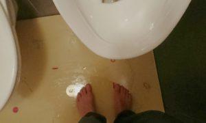 Barfuß auf nasser öffentlicher Toilette